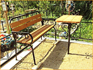 Кованая скамейка и столик на кладбище