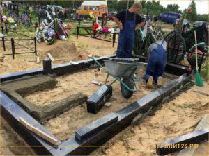 Специалисты занимаются установкой памятника из гранита